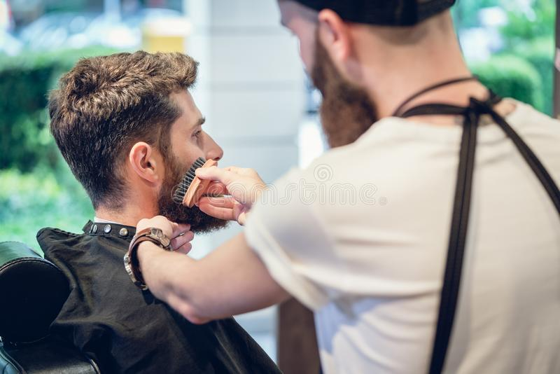 Primer de las manos de un peluquero experto que usa un cepillo imagenes de archivo