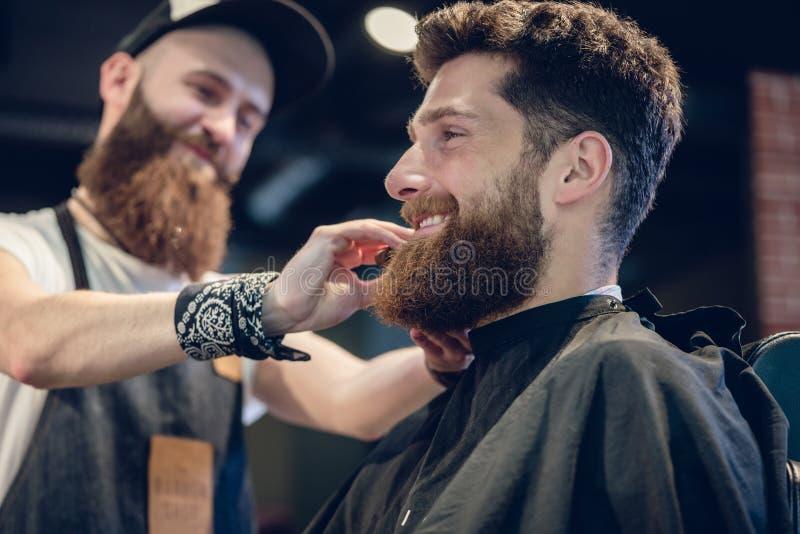 Primer de las manos de un peluquero experto que usa un cepillo imagen de archivo