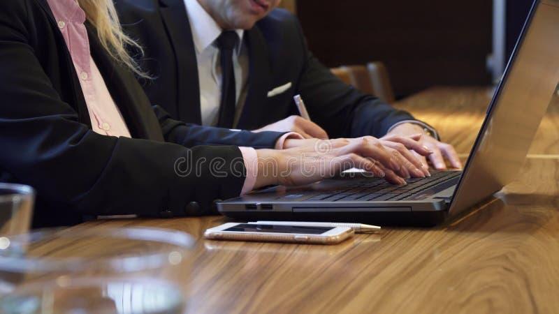 Primer de las manos de una mujer que mecanografía algo en el teclado de ordenador imagenes de archivo