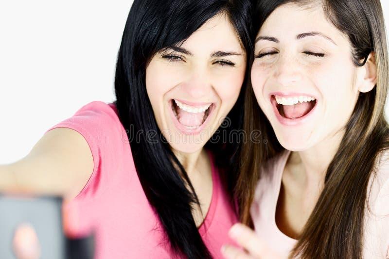 Primer de las muchachas que ríen que toma la imagen con el teléfono elegante imagenes de archivo
