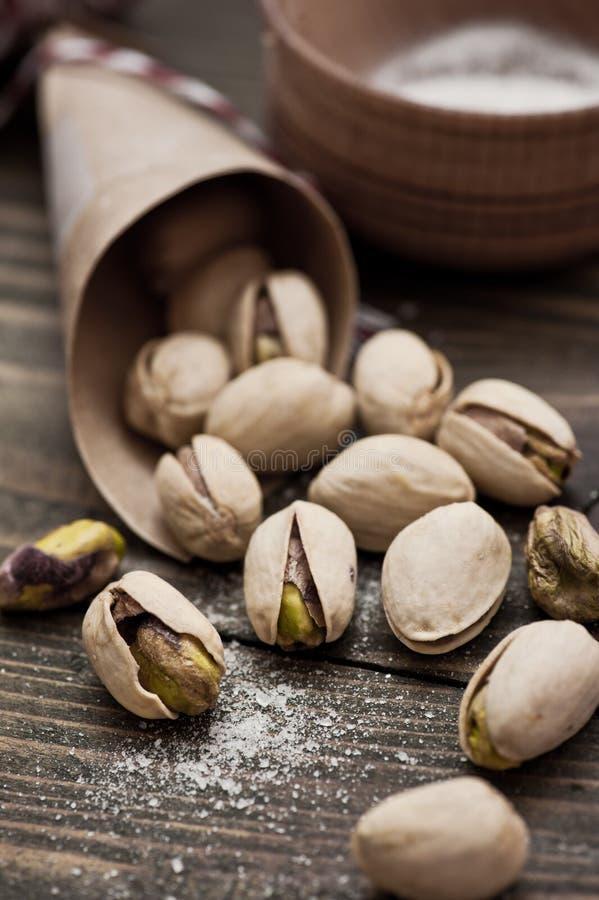 Primer de las nueces de pistachos en la tabla de madera foto de archivo