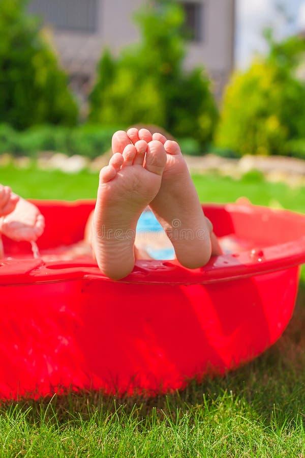 Primer de las piernas del niño en pequeña piscina roja fotos de archivo libres de regalías