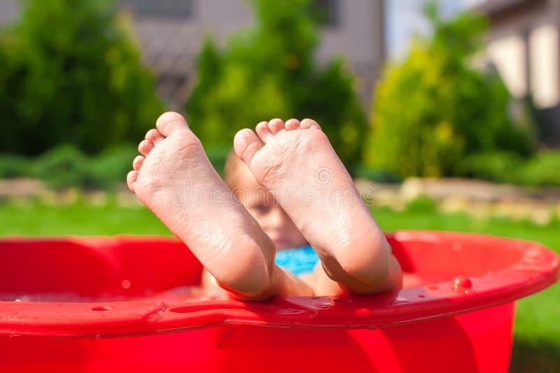 Primer de las piernas del niño en pequeña piscina roja imágenes de archivo libres de regalías