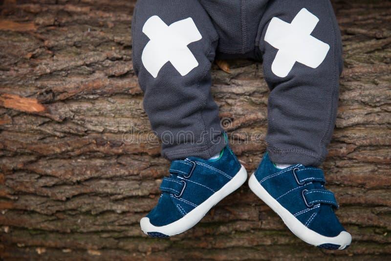 Primer de las piernas del ` s del bebé en zapatillas de deporte en el fondo de madera del árbol Pequeño niño que se sienta en el  fotos de archivo libres de regalías