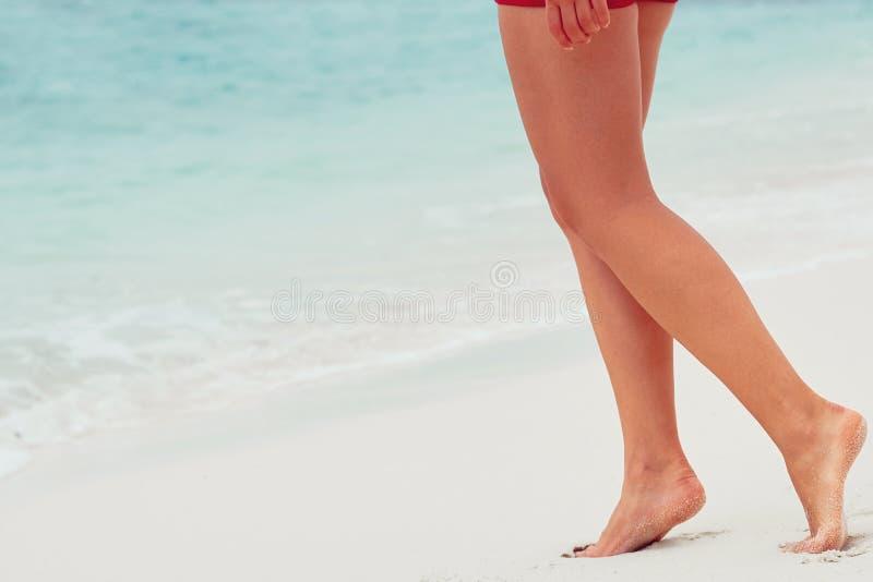 Primer de las piernas de la mujer que camina en la arena blanca que se relaja en playa Piernas magras y bronceadas atractivas Día fotos de archivo