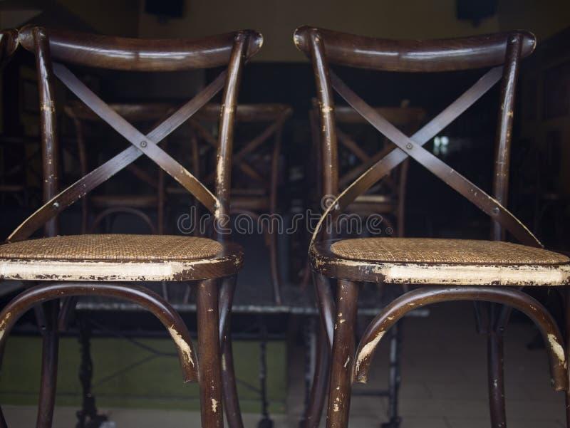 Primer de las sillas de madera resistidas de Brown colocadas y apiladas en un cuarto vacío imagenes de archivo