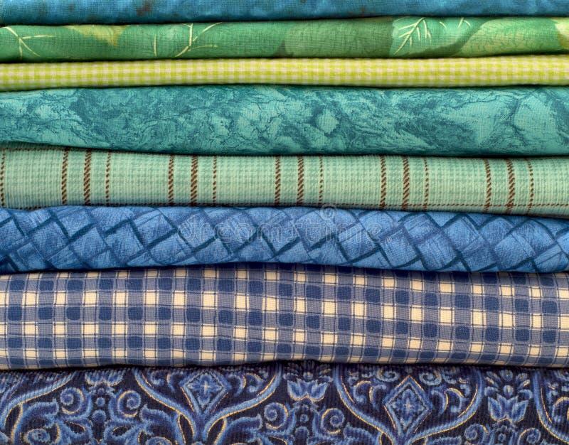 Primer de las telas azules y verdes apiladas horizontalmente fotografía de archivo