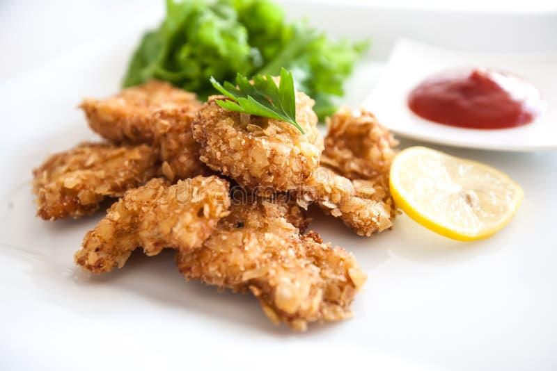 Primer de las tiras fritas curruscantes deliciosas en la placa blanca, pepitas de la pechuga de pollo de pollo con la ensalada de fotos de archivo libres de regalías