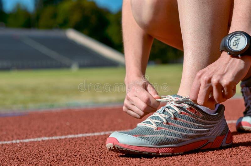 Primer de las zapatillas deportivas, atleta de sexo femenino del corredor que ata los cordones para entrenar y activar en pista d fotos de archivo libres de regalías