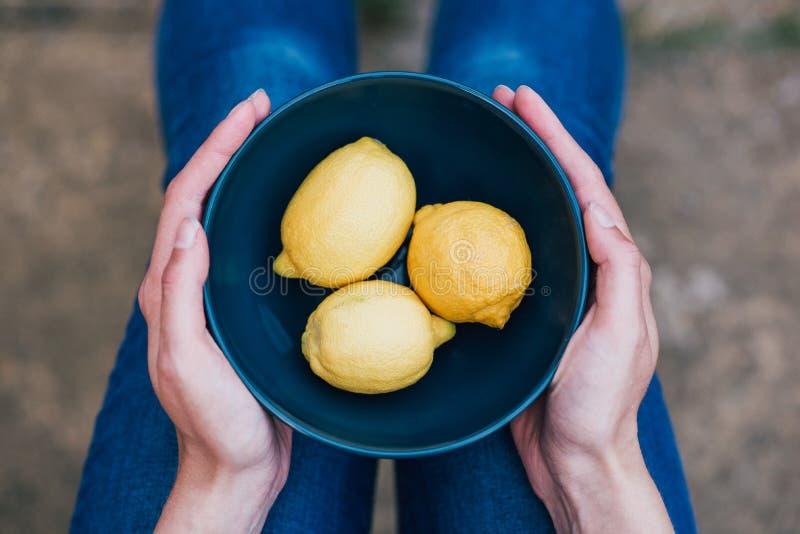 Primer de limones amarillos en un cuenco azul sostenido por una hembra fotos de archivo