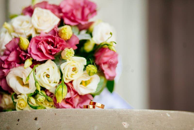 Primer de los anillos de bodas en el ramo de la boda del fondo de rosas de bayas y de verdes con lavanda imagenes de archivo