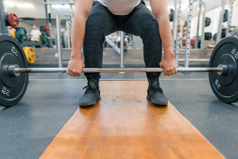 Primer de los brazos y de las piernas del hombre que ejercitan con el barbell en el gimnasio del deporte Atleta, levantamiento de fotografía de archivo