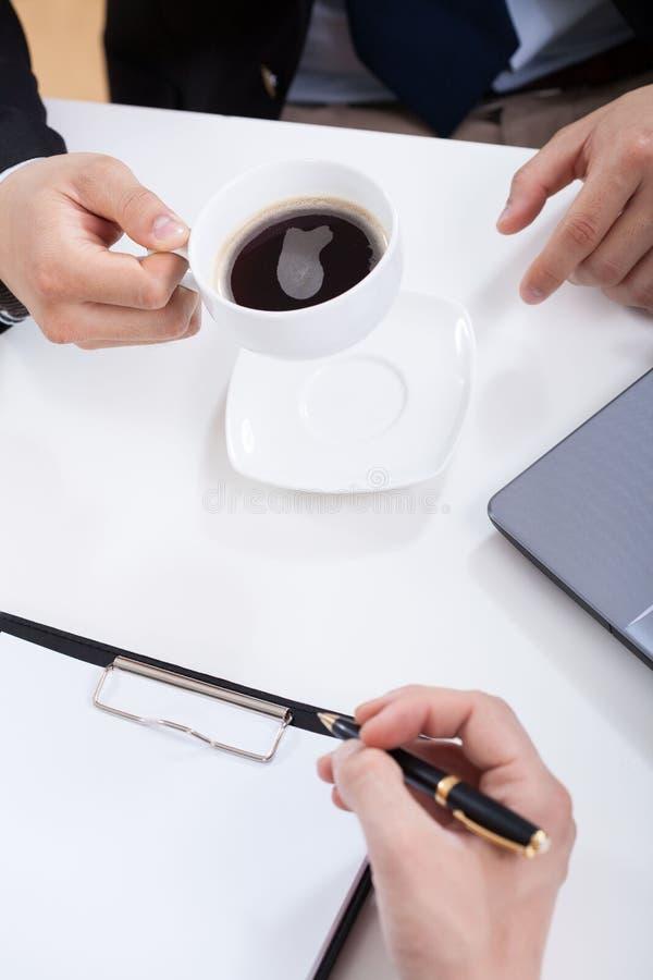Primer de los hombres de negocios que beben el café fotos de archivo libres de regalías