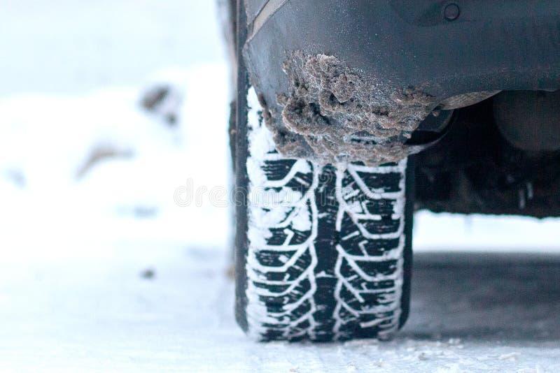 Primer de los neumáticos de coche en invierno en el camino cubierto con nieve imagen de archivo