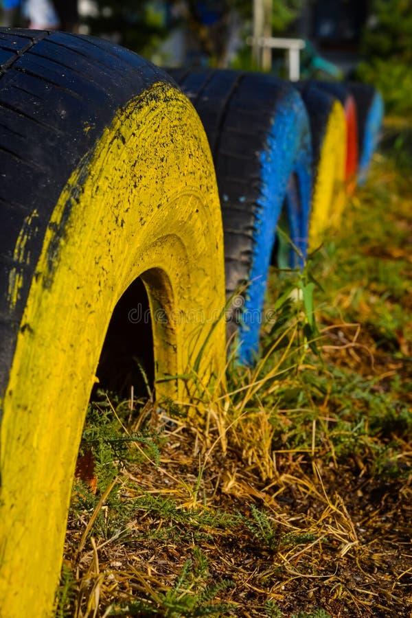 Primer de los neumáticos multicolores diseñados para el campo de deportes con un fondo suave imagenes de archivo