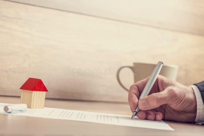 Primer de los papeles de firma del seguro de la mano masculina, contrato de la casa fotos de archivo libres de regalías