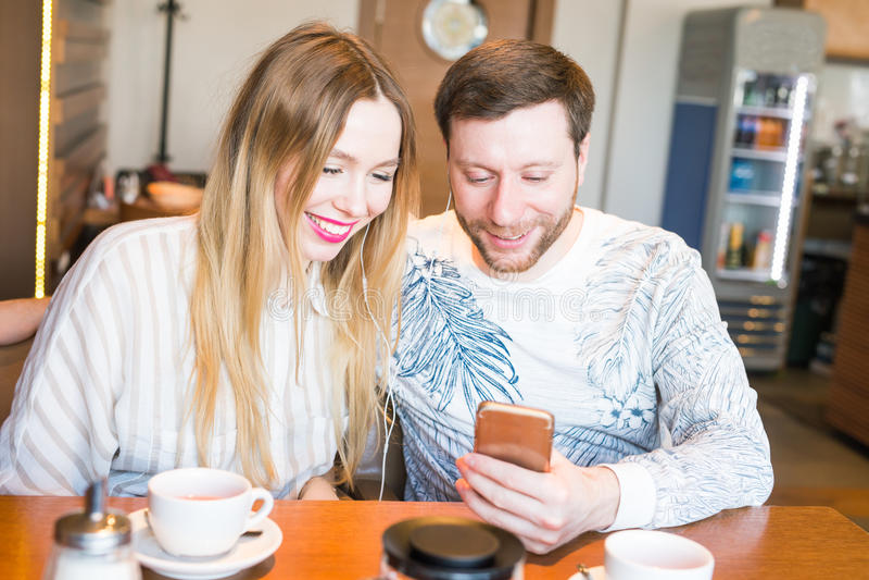 Primer de los pares que escuchan la música con el teléfono móvil en la barra de café Música que escucha del hombre y de la mujer  imagen de archivo libre de regalías