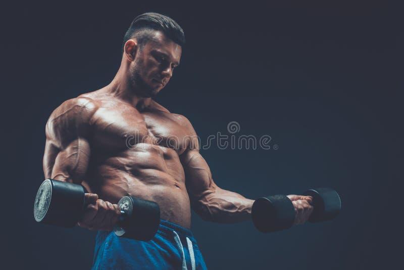 Primer de los pesos de elevación musculares de las pesas de gimnasia de un hombre joven en dar foto de archivo