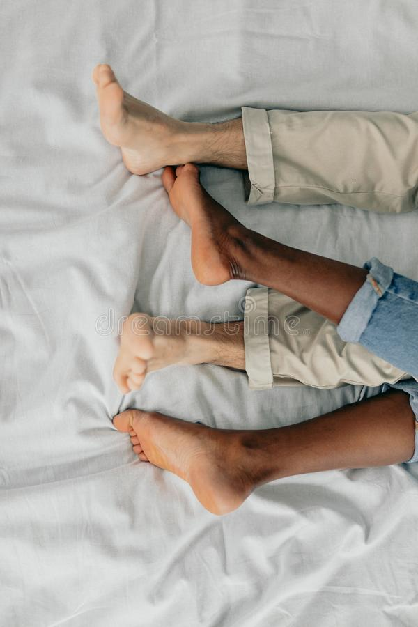 Primer de los pies de pares interraciales que duermen junto imagen de archivo