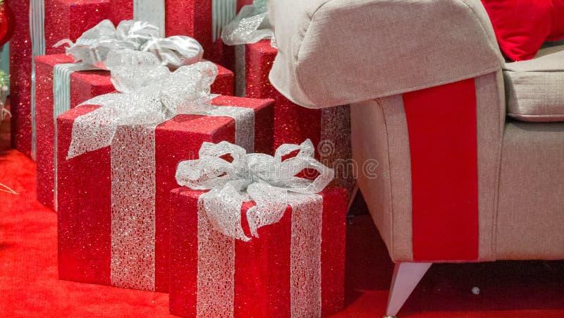 Primer de los regalos de la Navidad con la silla de Papá Noel en la derecha del bastidor foto de archivo