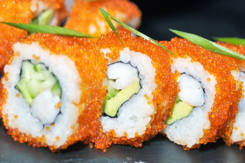 Primer de los rollos de sushi Comida japonesa en restaurante El rollo de sushi de California fijó con los salmones, la anguila, l foto de archivo