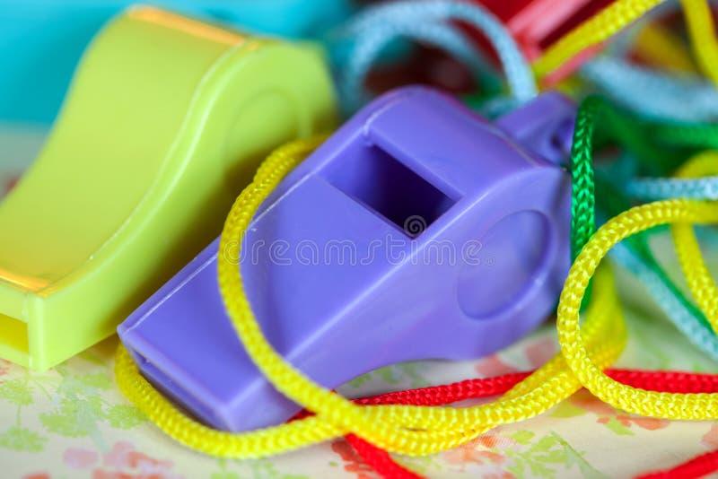 Primer de los silbidos plásticos coloridos de la diversión foto de archivo