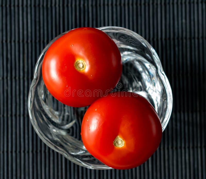 Primer de los tomates en un pequeño florero de cristal fotografía de archivo