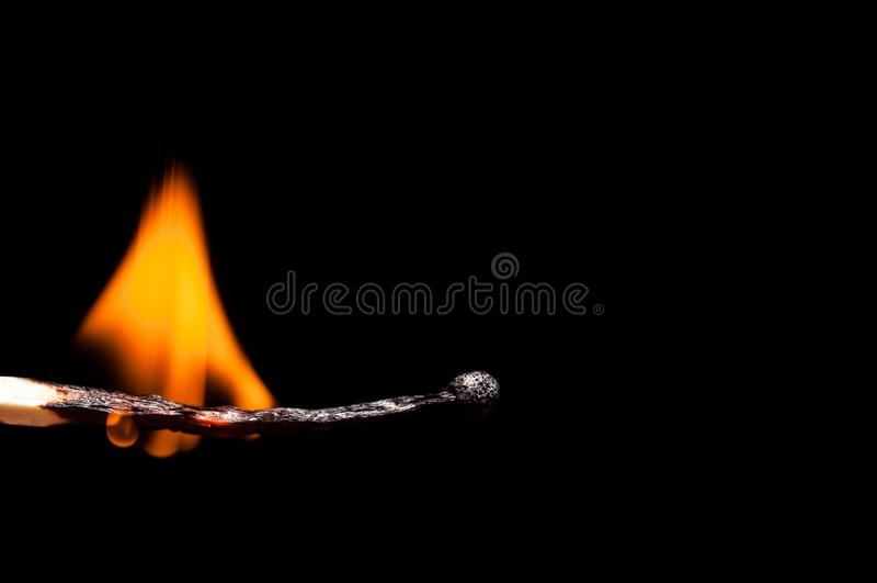 Primer de madera ardiendo-abajo del partido, en un fondo negro Tiroteo macro del aislante fotografía de archivo libre de regalías