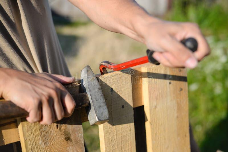 Primer de manos con la reparación de la palanca y del martillo foto de archivo