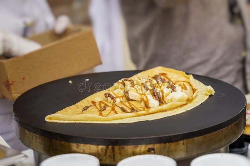 Primer de manos del cocinero en los guantes que preparan el crespón, crepe en el sartén con el plátano fresco, salsa dulce, nutel foto de archivo