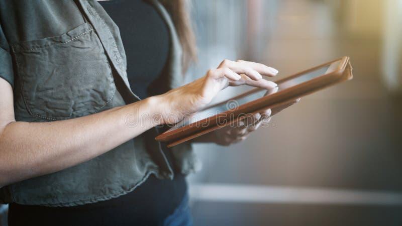 Primer de manos femeninas usando la tableta digital moderna dentro foto de archivo libre de regalías