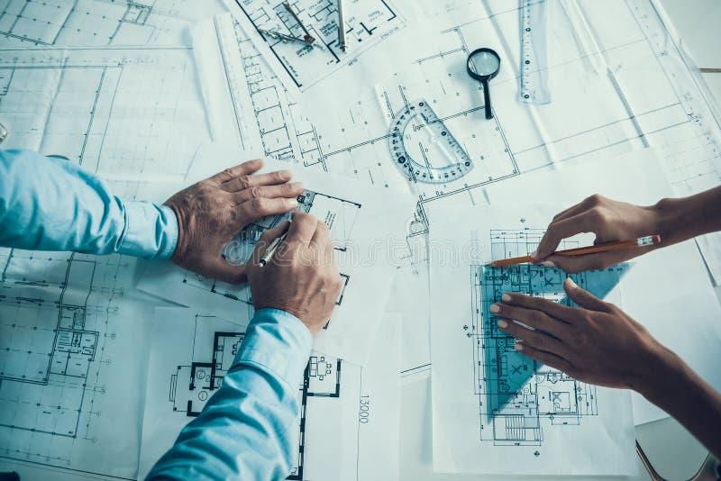 Primer de manos de los arquitectos que dibujan el modelo foto de archivo