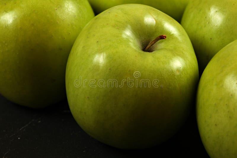Primer de manzanas verdes en el tablero negro, foto detallada - textura en la piel de la manzana visible fotos de archivo