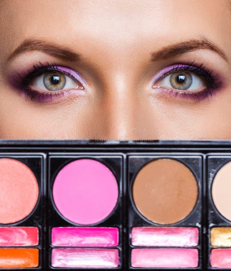 Primer de ojos hermosos con el equipo del maquillaje y el maquillaje atractivo fotos de archivo libres de regalías