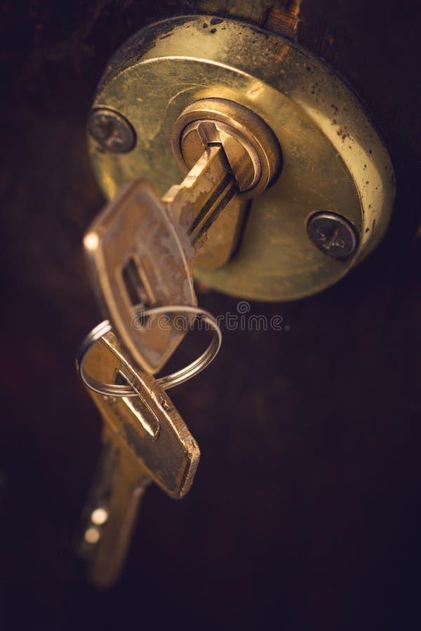 Primer de pares de llaves en cerradura de puerta de madera fotos de archivo