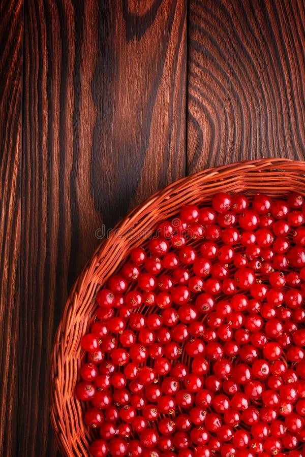 Primer de pasas rojas jugosas en un fondo marrón Una cesta llenada de la pasa sabrosa Bayas orgánicas nutritivas fotografía de archivo