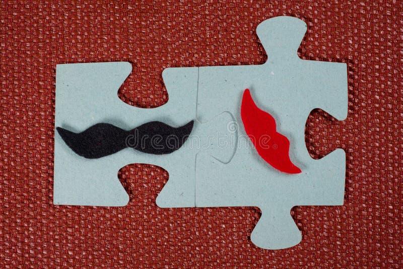 Primer de 2 pedazos de rompecabezas Un hombre simbólico con un bigote y una mujer con los labios El concepto de compatibilidad ps fotos de archivo