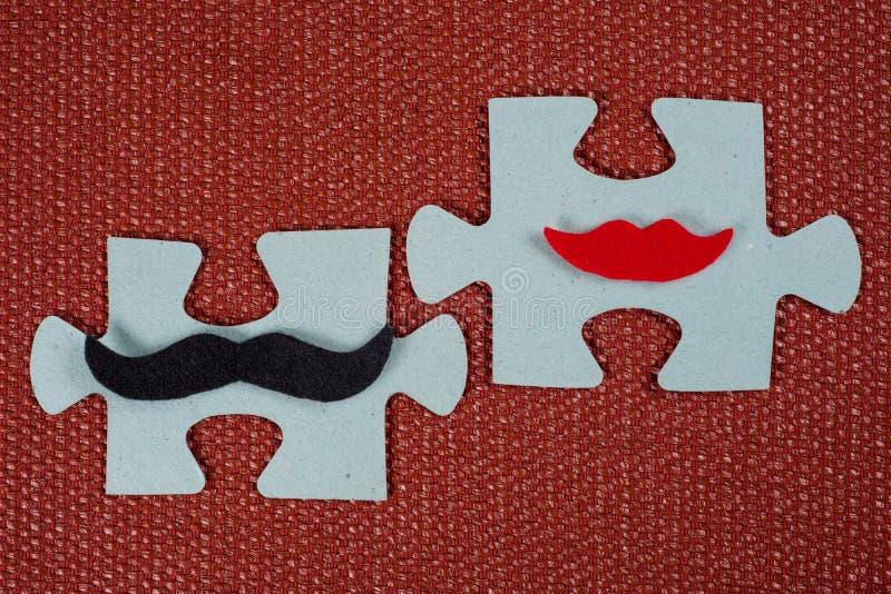 Primer de 2 pedazos de rompecabezas Un hombre simbólico con un bigote y una mujer con los labios El concepto de compatibilidad ps fotografía de archivo