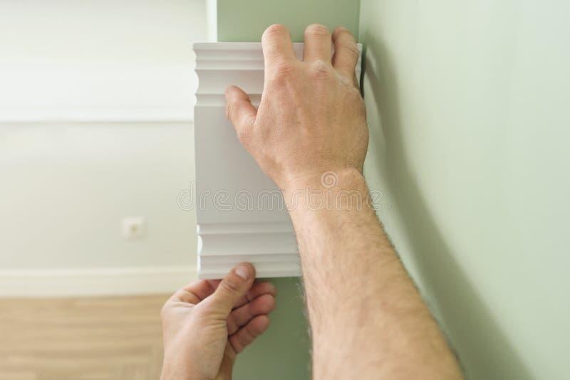 Primer de pegar el panel pintado blanco de madera del tablón en la pared, primer, carpintería, artesanía en madera, profesión, ge imagen de archivo