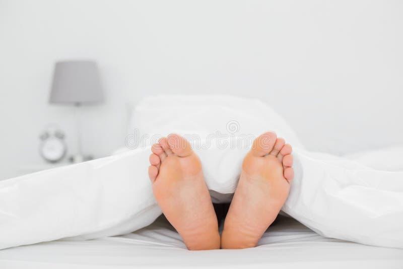 Primer de pies desnudos en cama imagenes de archivo