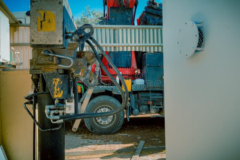 Primer de pistones hidráulicos de un camión que apareja que parquea con la máquina de elevación pesada del brazo de la grúa imagen de archivo libre de regalías