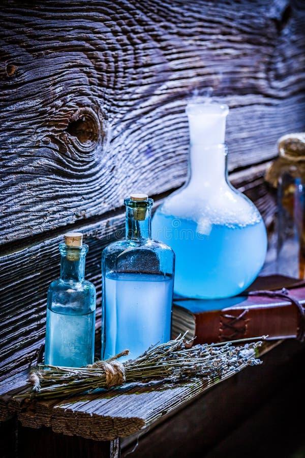 Primer de pociones azules mágicas en el estante de madera para Halloween foto de archivo libre de regalías