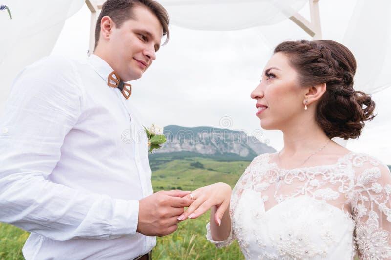 Primer de poner en los anillos en una boda al aire libre fotos de archivo libres de regalías