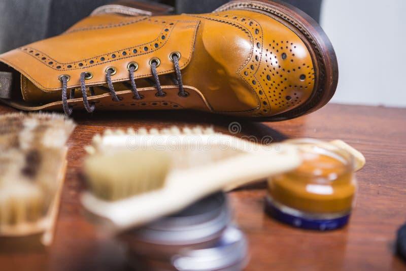 Primer de Tan Brogue Derby Boots masculina con la variedad de accesorios de la limpieza fotografía de archivo libre de regalías