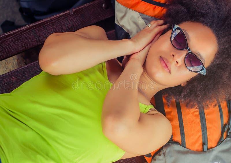 Primer de tomar una siesta turístico del backpacker femenino en un banco fotos de archivo libres de regalías