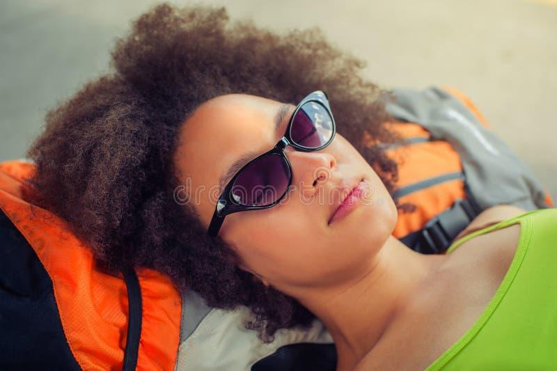 Primer de tomar una siesta turístico del backpacker femenino en un banco imagen de archivo libre de regalías