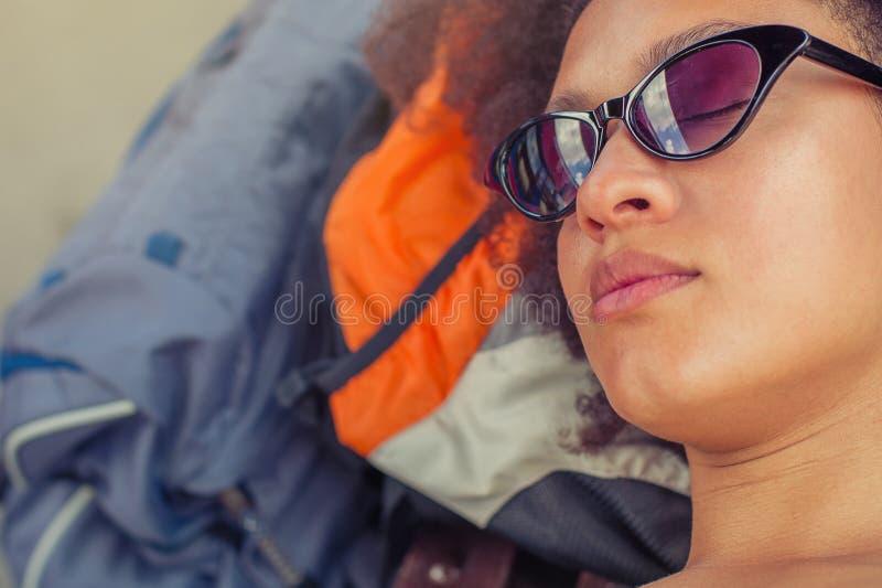 Primer de tomar una siesta turístico del backpacker femenino en un banco foto de archivo libre de regalías