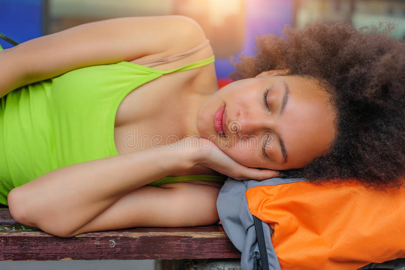 Primer de tomar una siesta turístico del backpacker femenino en un banco fotografía de archivo libre de regalías