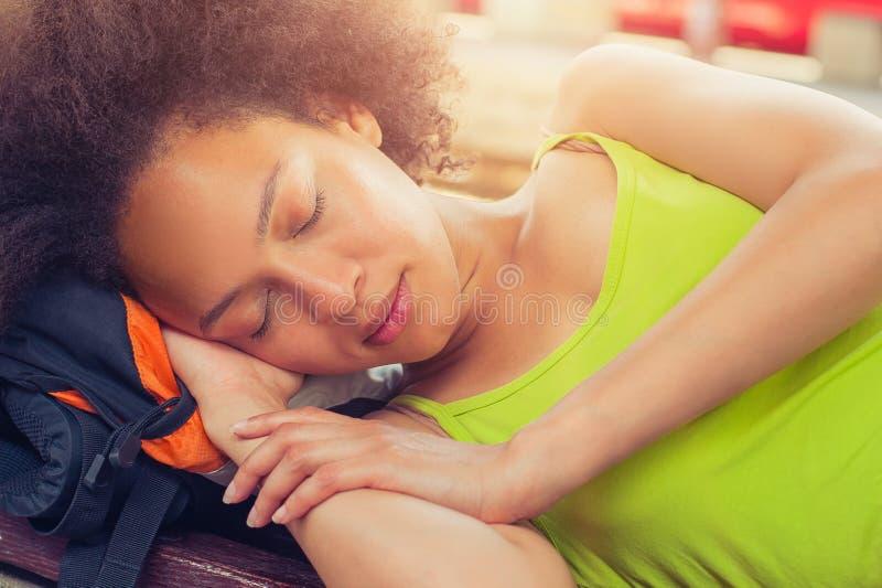 Primer de tomar una siesta turístico del backpacker femenino en un banco imágenes de archivo libres de regalías