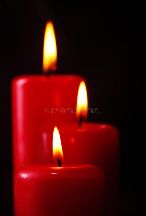 Primer de tres velas ardientes rojas contra fondo negro primer Copie el espacio fotos de archivo